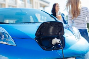 Blue electric vehicle being charged