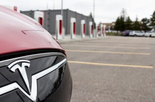 Red Tesla with a focus on the logo badge